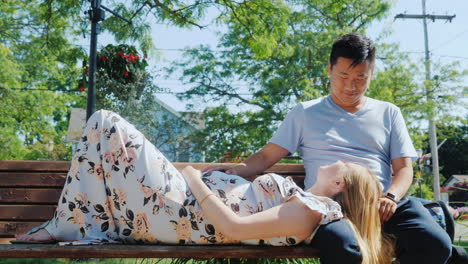 A-Pregnant-Woman-With-Her-Husband-Are-Resting-In-A-Park-On-A-Bench-In-A-Typical-Suburb-Of-Usa