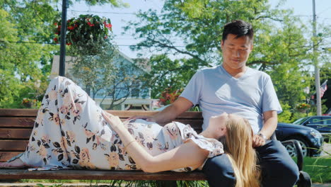 Asian-Man-With-A-Pregnant-Wife-Are-Resting-In-A-Park-On-A-Bench-Good-Time-Together
