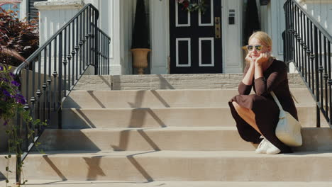 A-Woman-Sits-On-The-Steps-On-The-Porch-Of-The-House