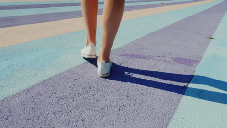 Follow-Shot-Of-Walking-Feet-In-Sports-Shoes-Walking-On-Colorful-Motley-Asphalt
