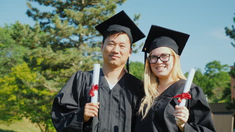 A-Portrait-Of-Two-Graduates---An-Asian-Man-And-A-Caucasian-Woman-In-The-Clothes-And-Caps-Of-The-Grad