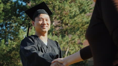 Successful-Asian-Man-In-Graduate-Clothes-Accepts-Congratulations-They-Shake-His-Hand