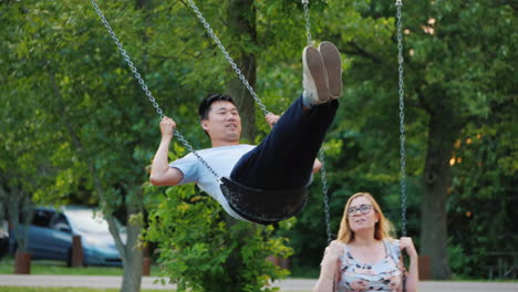 Young-Couple-Having-Fun-Swinging-On-A-Swing-A-Good-Time-Together-An-Active-Young-Family-Expecting-A-