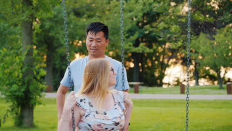 Multi-Ethnic-Couple---Asian-Man-And-Pregnant-Caucasian-Woman-Ride-On-A-Swing-Happy-Young-Family