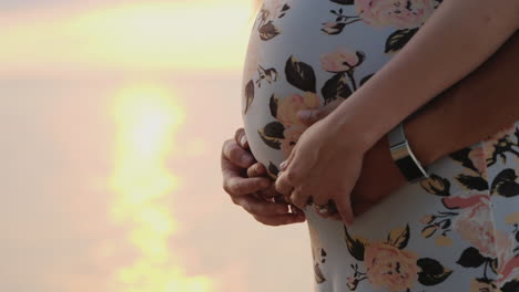 Male-Hands-On-The-Stomach-Of-A-Pregnant-Woman-Only-The-Stomach-And-Two-Pairs-Of-Hands-Are-Visible-In