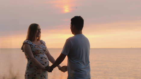 Multi-Ethnic-Malt-Couple-Holding-Hands-Against-The-Backdrop-Of-The-Sunset-Over-The-Sea-Asian-Man-And