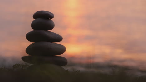 A-Hand-Lays-A-Stone-On-Top-Of-A-Tower-Of-Stones-Harmony-And-Balance-Concept