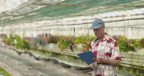 Researcher-Examining-Potted-Plant-At-Greenhouse-15