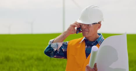 Angry-Engineer-Talking-On-Mobile-Phone-At-Windmill-Farm-Farm
