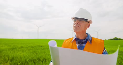 Engineer-Analyzing-Plan-While-Looking-At-Windmill-Farm-Eco-Energy-Concept-3