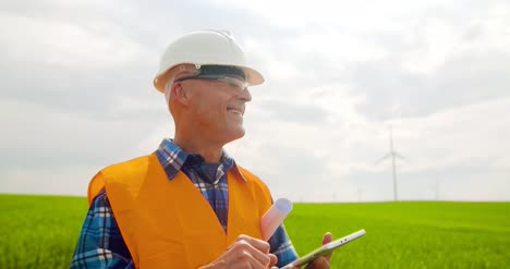 Smiling-Engineer-Using-Digital-Tablet-At-Windmill-Farm-Against-Sky