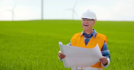 Engineer-Analyzing-Plan-While-Looking-At-Windmill-Farm-Eco-Energy-Concept-6