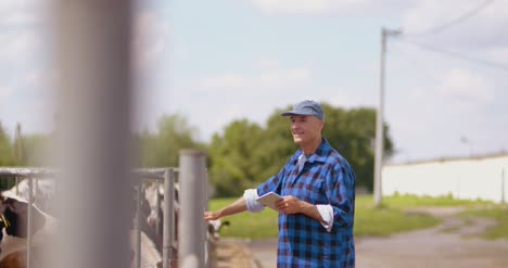 Farmer-Gesturing-While-Writing-On-Clipboard-Against-Barn-20