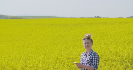 Farmer-Touching-Screen-Of-Digital-Tablet-At-Rapeseed-Field-2