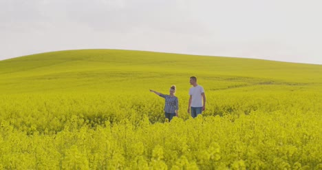 Farmers-Discussing-Over-Digital-Tablet-At-Rapeseed-Field-5