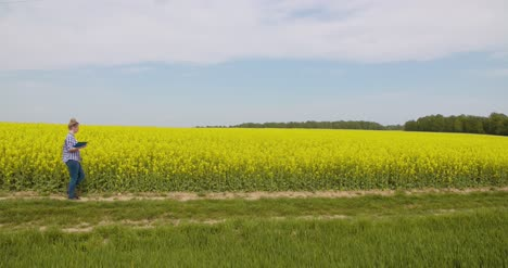 Confident-Female-Farmer-Writing-In-Clipboard-At-Rapeseed-Field-1