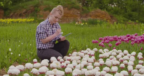 Female-Researcher-Walking-While-Examining-Tulips-At-Field-21