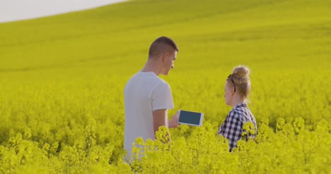 Farmers-Discussing-Over-Tablet-Computer-At-Rapeseed-Field-4