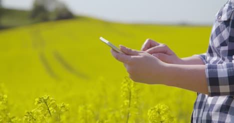 Farmer-Touching-Screen-Of-Digital-Tablet-At-Rapeseed-Field-13
