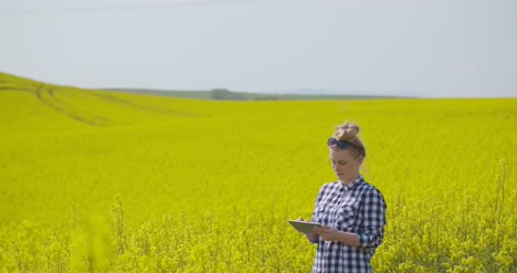 Farmer-Touching-Screen-Of-Digital-Tablet-At-Rapeseed-Field-15