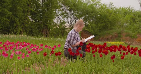 Female-Researcher-Walking-While-Examining-Tulips-At-Field-30