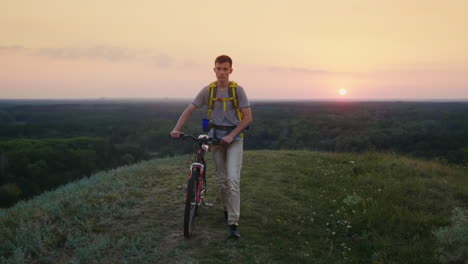 A-Tired-Teenager-With-A-Biker-Behind-His-Back-Drives-His-Bicycle-Along-The-Rural-Road-Steadicam-Shot