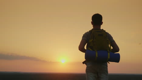 A-Young-Male-Tourist-With-A-Backpack-Looks-At-The-Horizon-Where-The-Sun-Sets-Back-View-4k-Video