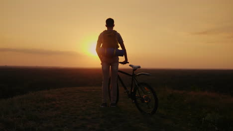 A-Man-With-A-Backpack-And-A-Bicycle-It-Stands-And-Looks-At-The-Horizon-Where-The-Sun-Sets-Cycling-An