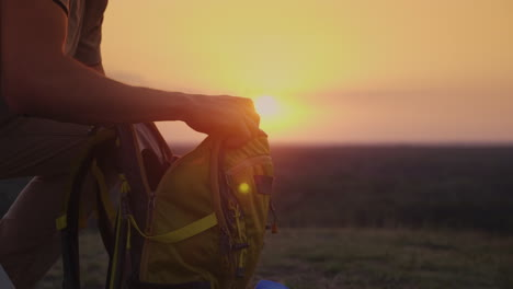 A-Man-Is-Packing-His-Backpack-At-Sunset-Preparing-For-A-Trip-Or-Trekking-4k-10-Bit-Video
