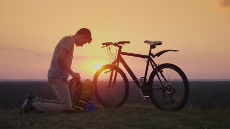 A-Young-Man-Puts-Things-In-A-Backpack-Sits-By-The-Bike-At-Sunset-4k-10-Bit-Video