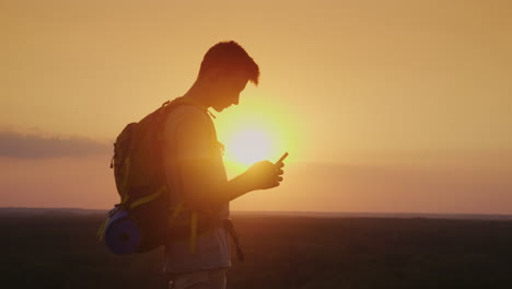 Always-And-Everywhere-In-Touch-A-Traveler-With-A-Backpack-Uses-A-Smartphone-Silhouette-On-Sunset-Bac