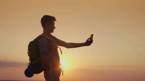 A-Teenager-With-A-Backpack-Pictures-Himself-With-A-Phone-Against-The-Setting-Sun-Tourism-And-Travel-