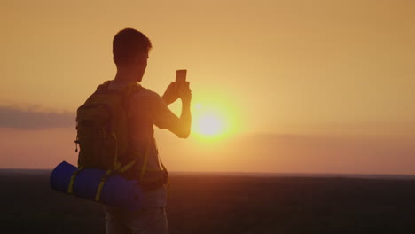 A-Young-Man-With-A-Backpack-Is-Taking-Pictures-Of-A-Beautiful-Landscape-At-Sunset-Silhouette-On-Oran