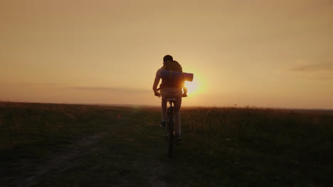 A-Biker-With-A-Backpack-Rides-Uphill-Along-A-Rural-Road-In-The-Rays-Of-The-Setting-Sun-Slow-Motion-V