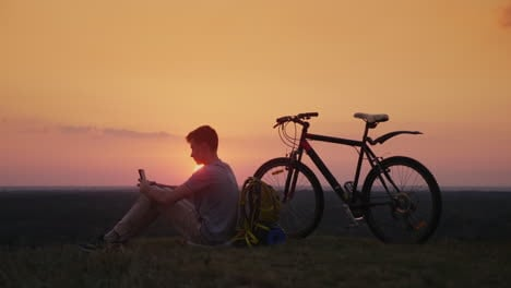 The-Teenager-Uses-A-Smartphone-Sits-Near-His-Bike-And-Backpack-At-Sunset