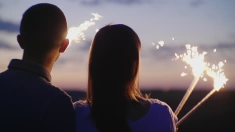 Young-Couple-Having-Fun-With-Fireworks-They-Look-Ahead-In-Front-Of-Them-Fireworks-Are-Burning-In-The