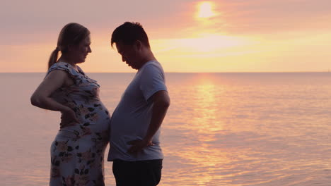 A-Young-Man-And-His-Pregnant-Wife-Have-Fun-Measure-Their-Stomachs-Happy-Time-Together