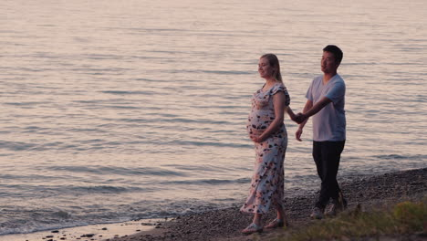 Multi-Ethnic-Couple---Asian-Man-And-His-Pregnant-Wife-Are-Walking-Along-The-Seashore