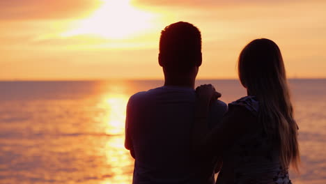 Multi-Ethnic-Couple-In-Love-Admires-The-Sunset-Over-The-Ocean
