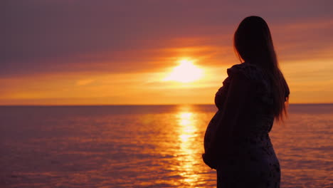 Silhouette-Of-A-Young-Pregnant-Woman-On-A-Sunset-Background-Over-The-Ocean