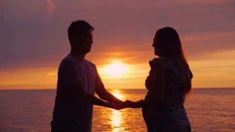Side-View-Of-An-Asian-Man-Holding-His-Pregnant-Wife-s-Hands-In-The-Background-Of-Sunset-Over-The-Sea