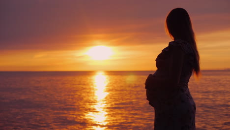 Young-Pregnant-Woman-With-A-Big-Belly-Looks-At-The-Majestic-Sunset-Over-The-Sea