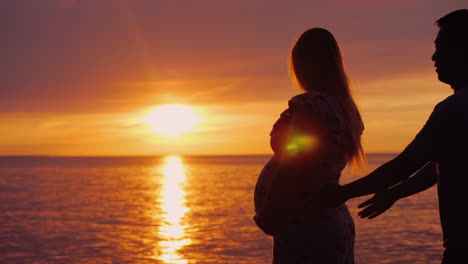 Asian-Man-Hugs-His-Pregnant-Wife-On-A-Sunset-Background-Over-The-Sea