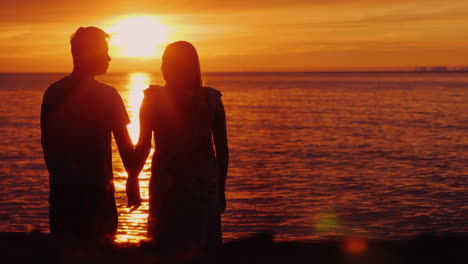 Multi-Ethnic-Couple-In-Love-Holding-Hands-On-The-Background-Of-The-Sea-Where-The-Sun-Sets-Beautifull