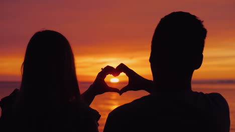 Silhouettes-Of-A-Young-Couple-Hands-Show-The-Shape-Of-The-Heart-Against-The-Backdrop-Of-The-Sunset-O
