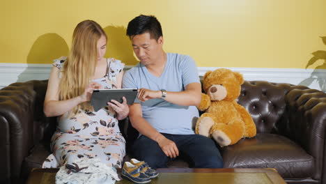 Young-Multi-Ethnic-Couple-Orders-Clothes-For-An-Unborn-Baby-Use-A-Tablet