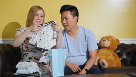 A-Pregnant-Woman-With-Her-Husband-Looks-At-Just-That-Things-Bought-For-The-Baby-Expecting-A-Baby-Buy