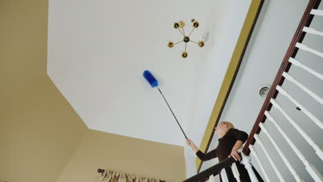 A-Woman-Cleans-The-Cobwebs-And-Debris-On-The-Ceiling-Near-The-Chandelier-Big-House-Cleaning