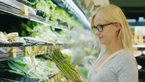 Middle-Aged-Woman-Chooses-Greens-In-The-Vegetable-Department-Of-The-Supermarket