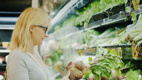 Young-Woman-Picks-Beets-In-The-Vegetable-Department-Of-The-Store